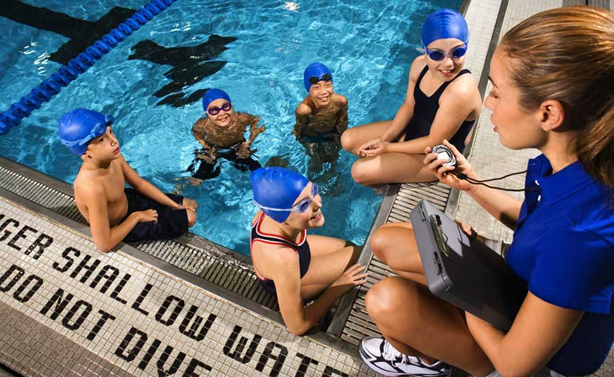 Photo of a woman coaching age group swimmers.