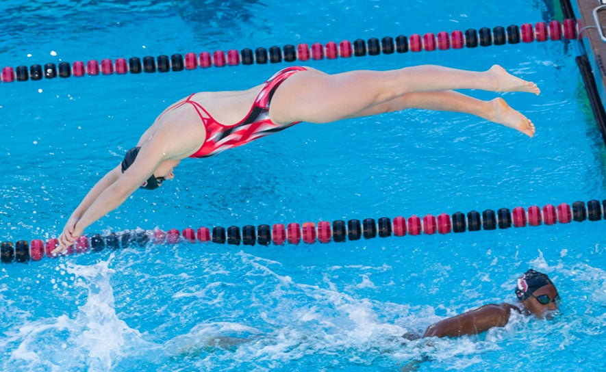 Katie Ledecky dives in swimming a relay for Stanford University.